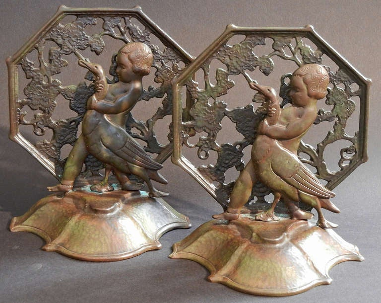 Beautifully detailed, with a gorgeous deep patina, this rare pair of bronze bookends by Oscar Bach depict girls holding geese by the neck, like something out of a charming nursery rhyme.  The figures were cast separately from and placed in front of