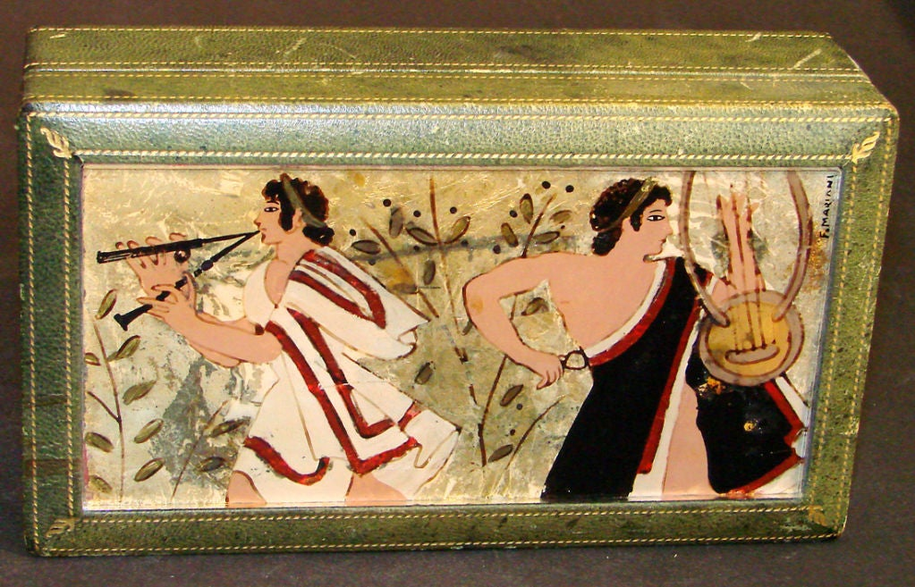 Beautifully painted and gorgeously crafted, this very fine hinged box features an églomisé glass panel depicting classical male figures with lyre and panpipes over a gold foil ground, signed by F. Mariani. The box exterior is covered with green