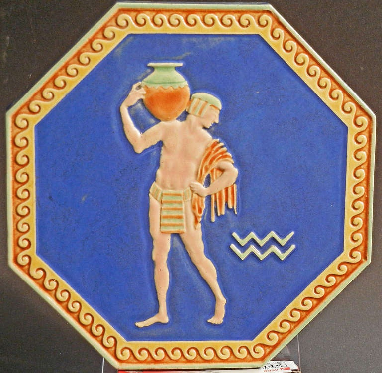 Beautifully sculpted and glazed in tones of indigo, straw and burnt orange, this very fine and rare octagonal tile was made in Italy. Depicting a nude male water carrier in Egyptian dress, this piece gives evidence of the Western world's infatuation