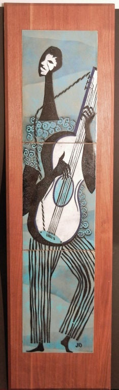 Superbly crafted and beautifully mounted on a gorgeous plank of American walnut, this class midcentury enameled panel depicts an African American man playing the guitar, all on a field of pale blues and grays.  The lambswool texture of the player's