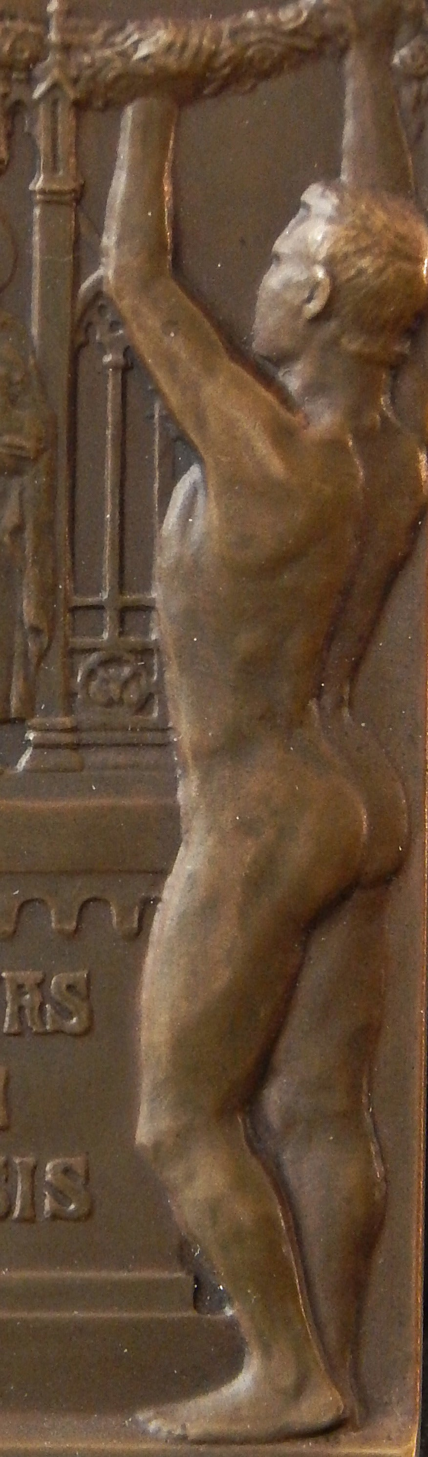 Depicting two male nudes lifting a garland framing Medieval images of the two patron saints of Leipzig University -- St. Laurentius and John the Baptist -- this rare and beautiful bronze relief was sculpted by Max Lange in 1909. The University, the