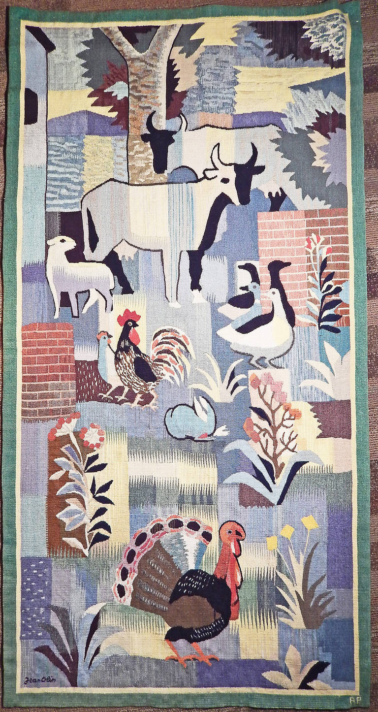 A brilliant and important example of Art Deco design, this wool tapestry was designed by Jean Olin and executed by the Aubusson tapestry works in France. The stylized farm animals including turkey, cow, rabbit and goose are intermixed with flowering