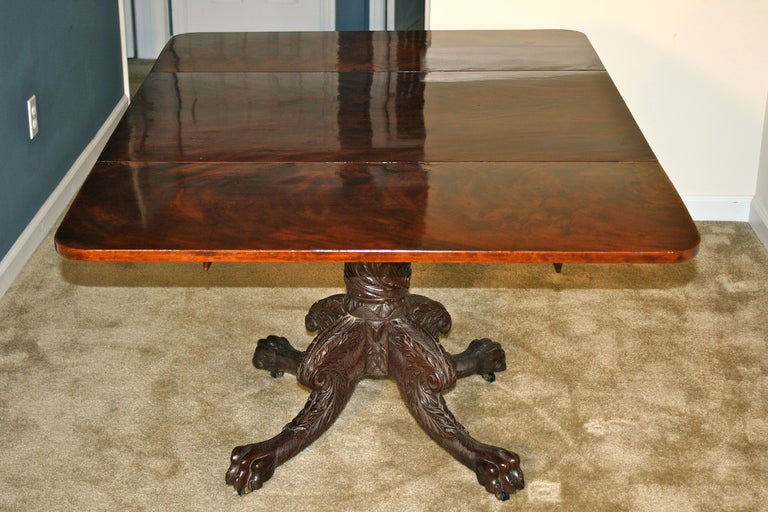 A Santo Domingo mahogany topped and leafed small dining, breakfast, or library table;  with a very finely and profusely hairy- carved pedestal and four legs ending in animal paws on casters.  With leaves down its top measures 40 inches x 29 inches.