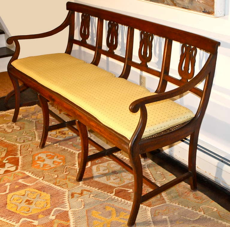 An Italian cane seated fruitwood quadruple lyre back settee and accompanying side chair. The lyre forms are actually pairs of swans' necks with a central inlaid column, simulating strings. Klismos legs with h-stretchers on both settee and chair.