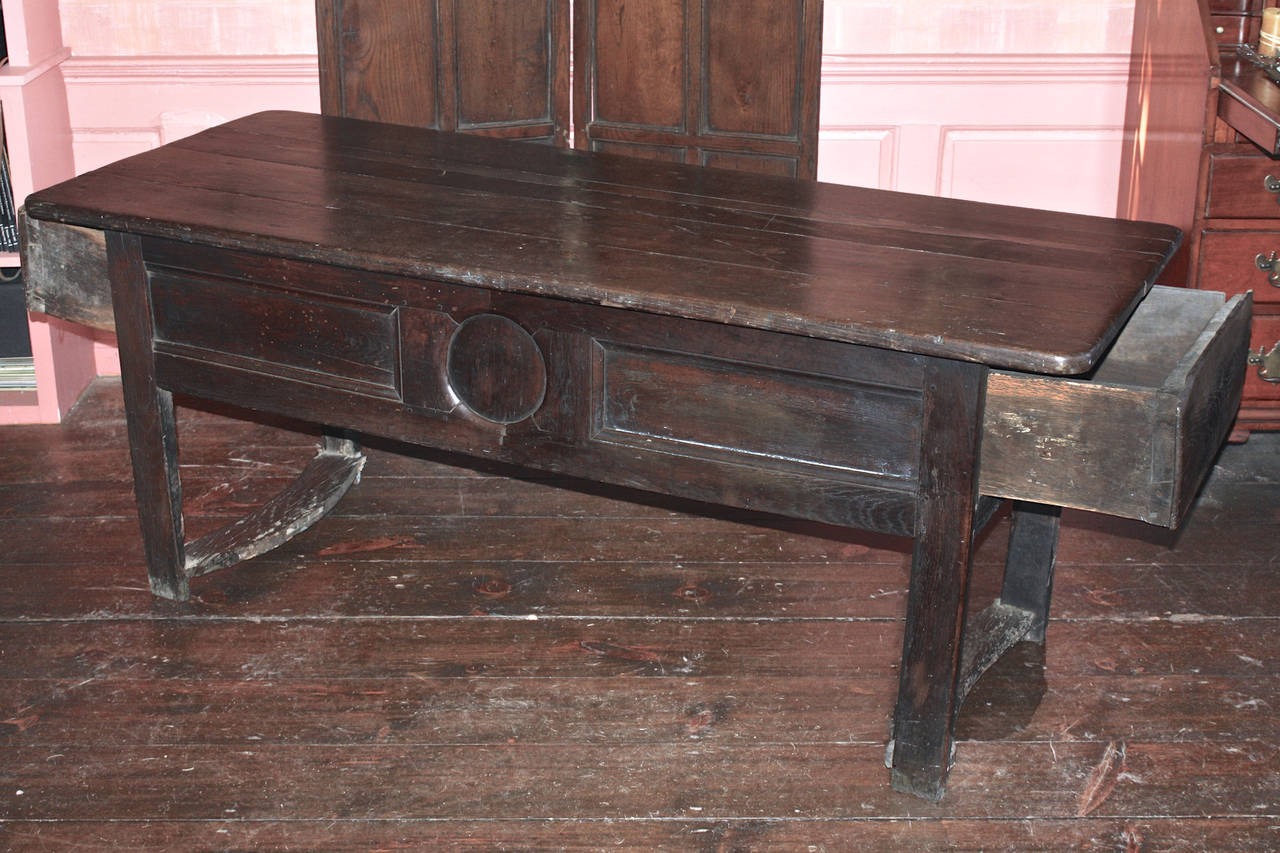 A hand hewn George I period chestnut refectory preparation or serving table, which may have been originally made to serve as a kitchen dough table; with apron drawers at each end for dough storage.  Its end legs are joined by concave flat