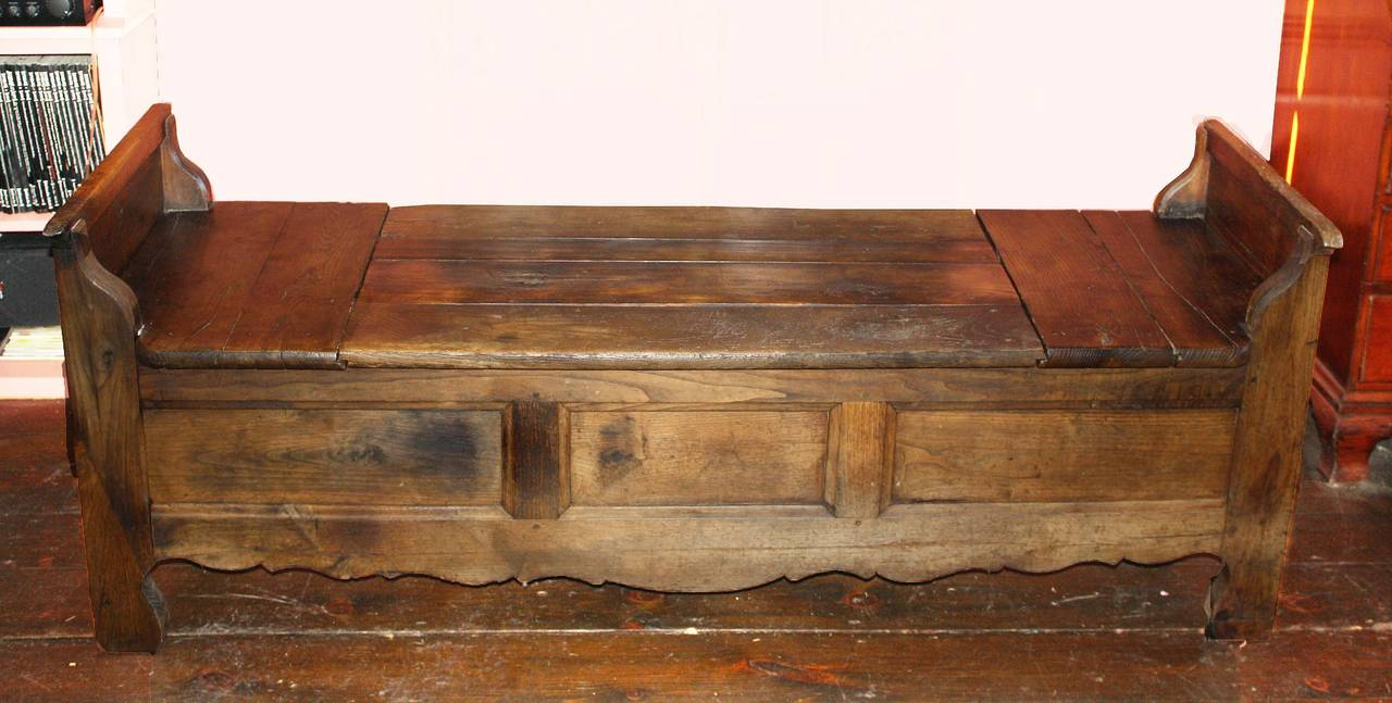 A Louis XIV period Provençal oak bench with trap door hidden coffer; further concealed by an upholstered seating cushion.  Paneled front and sides, with a scalloped frontal apron.  A useful hall, kitchen or bedroom bench with storage capacity.  An