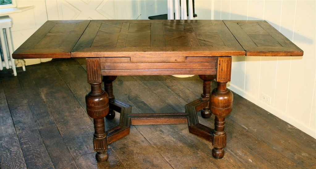 A Jacobean (James I) Revival oak draw-leaf center table; suitable as a writing, sofa back, or dining table for four.  The unusual carved stretcher formation, the 'bulb' leg turnings, and the block fluting; all evidence early application of Machine
