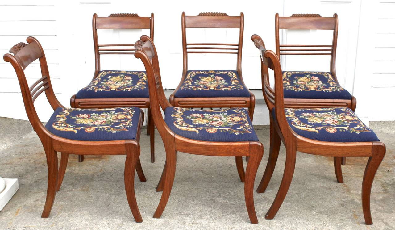 Six gadroon crested padauk klismos sabre-legged dining chairs, with hand-stitched needlepoint slip seats in mint condition. Attributed to Antoine Gabriel Quervelle, French trained Philadelphian furniture maker. Six of a very large set of side