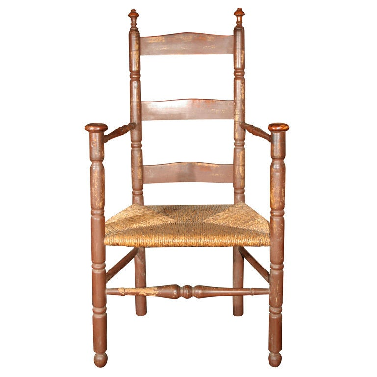 A rush seated, ochre painted, slat-back armchair, characteristic of Coastal Massachusetts; possibly as far South as the Islands off the Cape. Surface appears quite old or even original and is retouched only in areas of skilled repair. Hand wear has