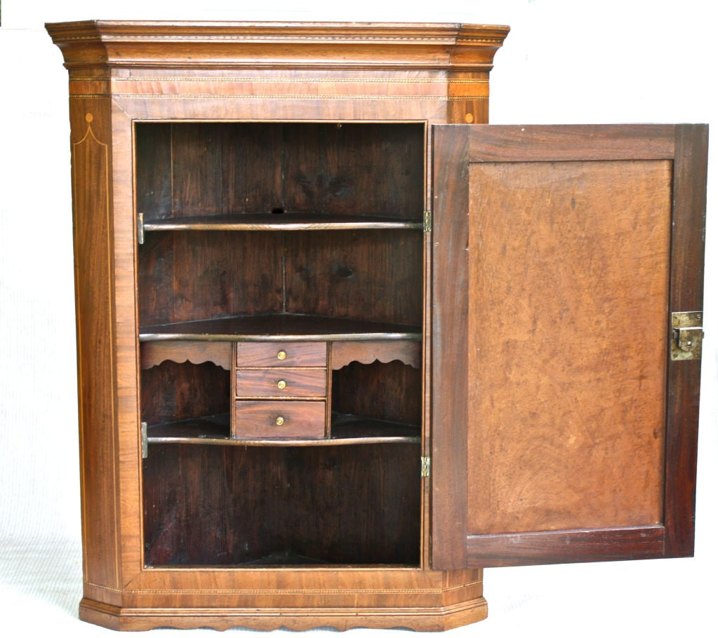 For wall mounting, a crossbanded and moulded mahogany corner cabinet with complex and intricate inlays; including an oak leaf door plaque. Three shelves inside, with three small drawers backed by a hidden compartment. The hardware and keyed working