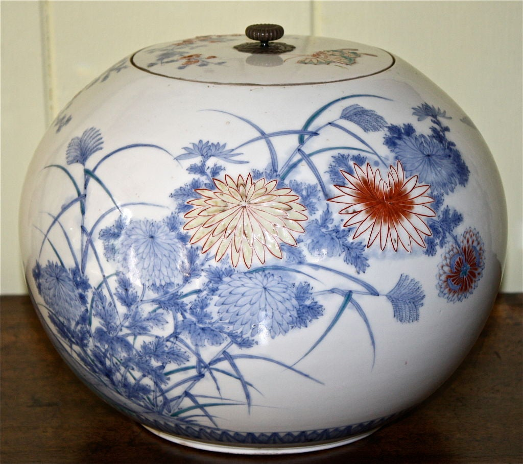 A Japanese porcelain water pot or 'mizusashi', of melon jar 'shonzui' form. Shonzui was a Japanese potter who worked in China in the 16th century. Decoration is of Kakiemon style, with pheasants amid prunus and blossoms; primarily blue and white,