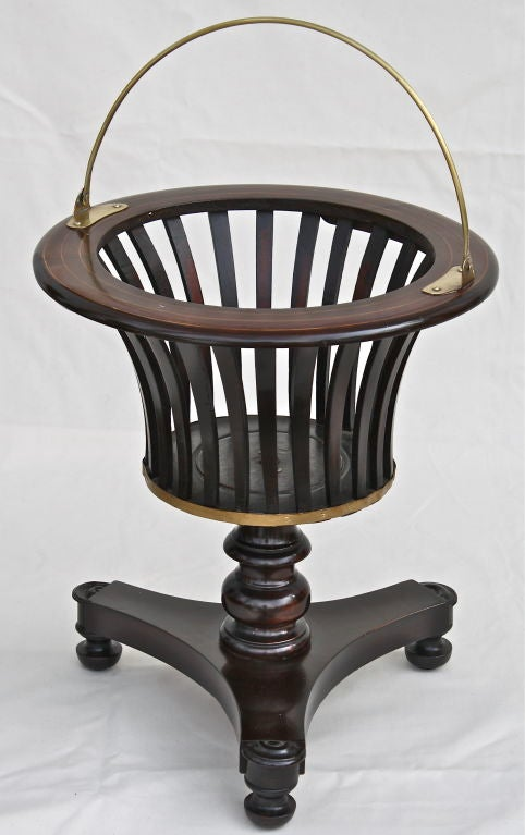 A finely inlaid mahogany slatted urn on pedestal and tripod base. Polished brass semi-circular carrying loop, urn base trim, and interior conforming brass pot. For table-side wine service, holding up to three bottles. Alternative use today as a