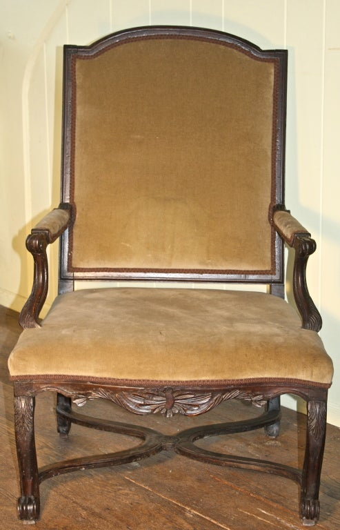 A hand-carved walnut open armchair with 'X' or flat Curule-form stretchers joining its four legs; made during the period between the reigns of Louis XIV and Louis XV (1715-1723), when Philippe d'Orleans was Regent. Tablet-back crest rail and
