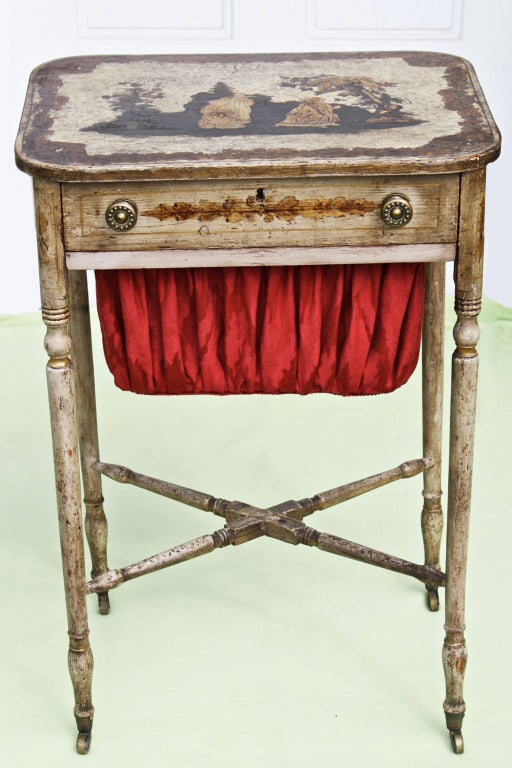 An American Federal period needlework or sewing table from Baltimore.  Lockable drawer, slide accessible cloth 'purse', turned cross stretchers; with original painted surface and brass casters. The stenciling on all four friezes and corners, and