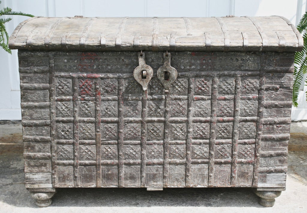A massive wooden iron strapped and hand tooled metal plated coffer or trunk, raised on inverted bun feet; with hand-forged double padlock hardware and side handles. Ex: an extensive private collection of Iberian and North African artifacts and