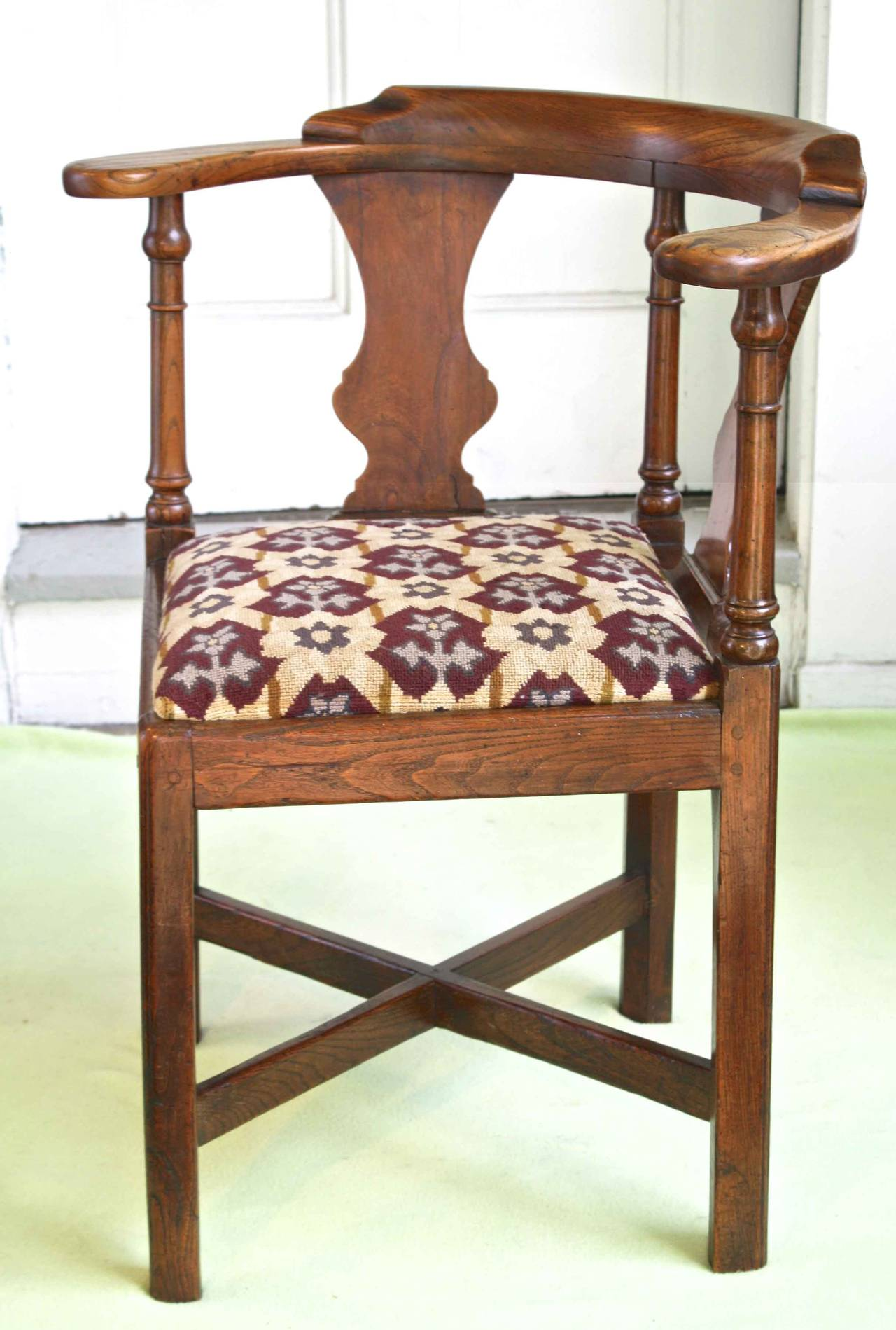 An early George II period elmwood 'country house' corner chair; with urn splats, flat paddle arms, and plain cross-stretchers. Striking geometric stylized floral needlepoint covered slip seat. Likely of Yorkshire origin.