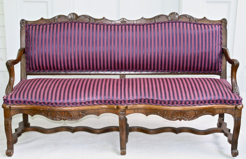 A slightly diminutive carved walnut canapé or settee, made at the outset of the reign of the Empress Maria Theresa.  Though its dating precedes the Franco-Austrian alliance,  Regence and early Louis XV period French stylistic influences are