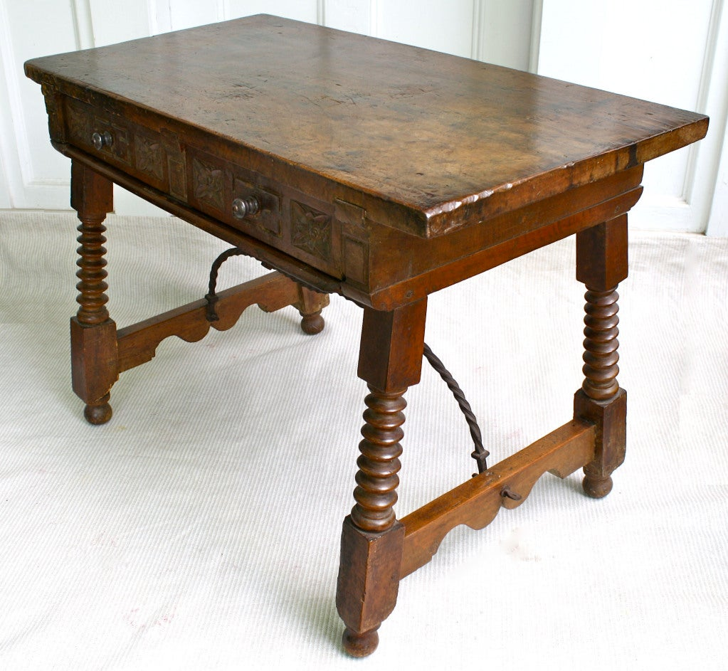 An Iberian walnut provincial splayed leg trestle-form side table, with wrought iron bent twisted rods attached to the wooden side stretchers; in the Castilian Baroque manner.  Two frontal frieze drawers, with foliate carved facings, allow for usage