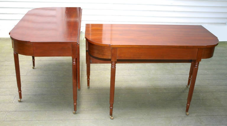 A New England Sheraton dining table in two parts, generously seating six or up to eight, if needed.  Of Connecticut or Rhode Island origin.  Recessed quarter-round cut corners, veneered friezes, with eight very finely readed legs;  including two