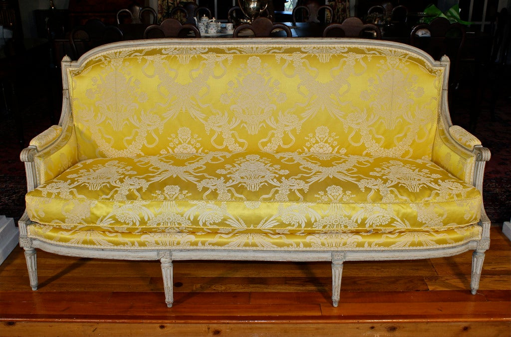 A three-seat canapé en peinte (settee in original paint) upholstered in yellow  Scalamandre silk damask.