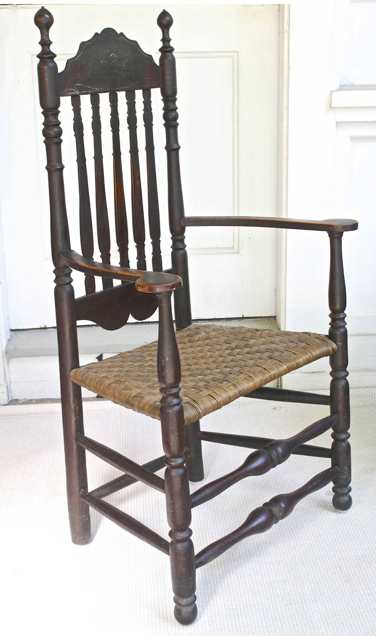 An exemplary American maple bannister back armchair with copious ring turnings, scalloped crest and lower back rails, in worn dark umber  paint; with a very old, appropriate and serviceable woven splint seat.  Of Massachusetts coastal origin and
