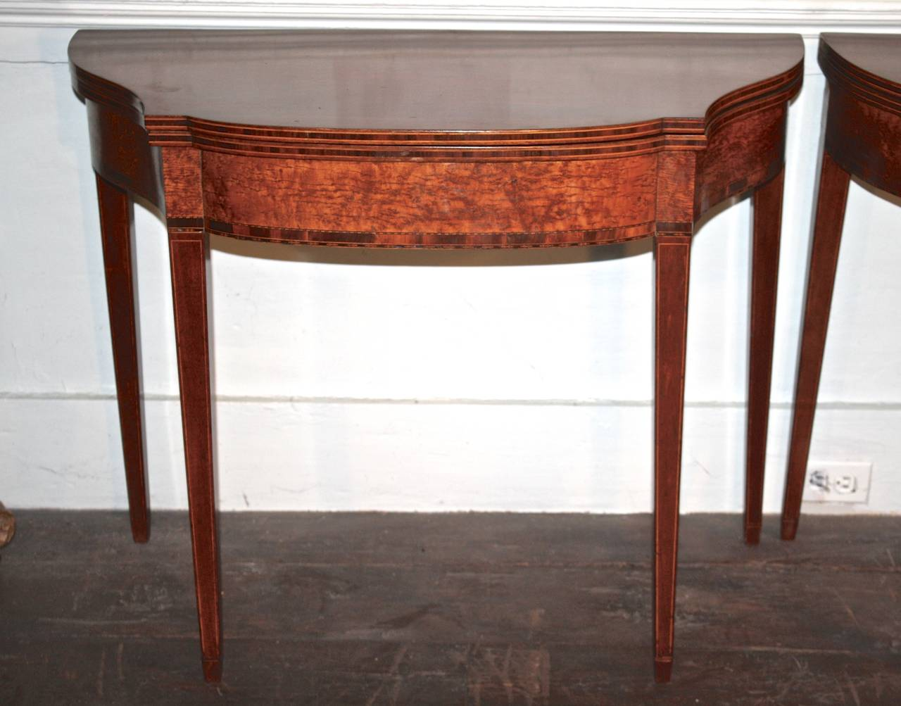 An intricately detailed matched pair of American Hepplewhite manner fold-over swing legged game tables.  Each opens flat to a serpentine 35 x 36 inch bowed four sided top.  Meticulously fine satinwood and ebony inlays, contrasting veneer bandings,