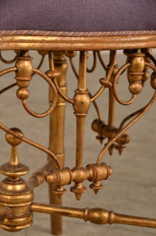 A charming Belle Epoque period gold leaf tabouret (stool) from France c. 1895. Look at the fanciful carved detail on this piece where all the wood is embellished with gold leaf. Each of the four splay shaped legs are connected by a cross stretcher