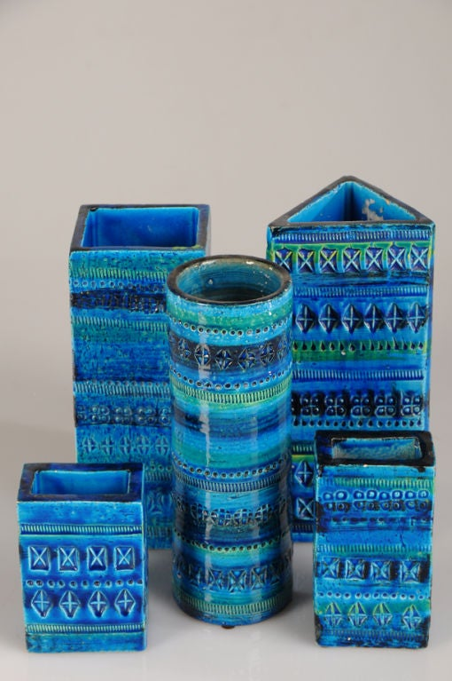 A collection of five assorted glazed earthenware vessels in a gorgeous blue and green from Italy c. 1965. Please notice the unusual variety of incised patterns present on each of these different shapes. The cylinder, the triangular shaped vessel,