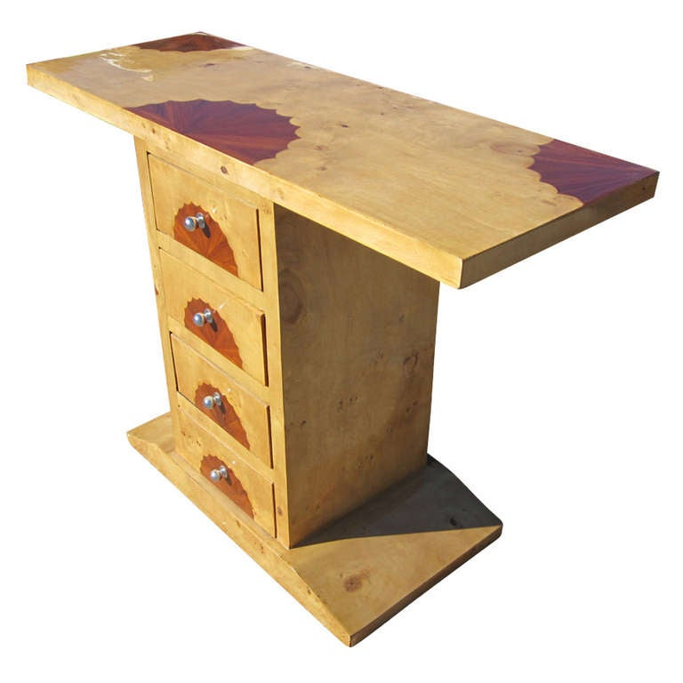Art Deco table features a maple and burl top. The base is a tapered, rectangular form with three drawers accented with round, metal, drawer pulls. The top and drawers have distinctive scalloped wood inlays.