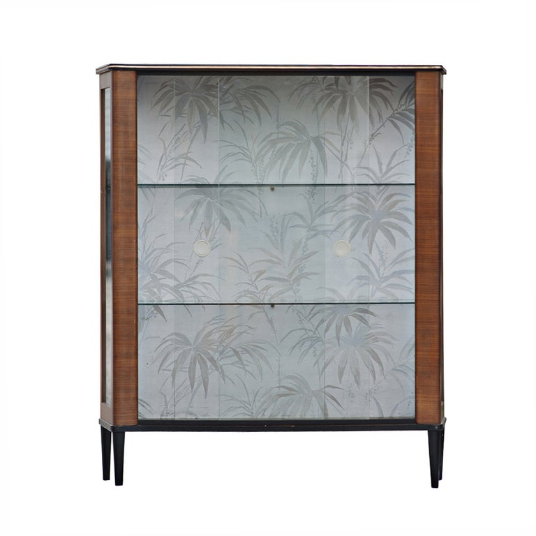 A lovely mid century modern curio display cabinet with two glass shelves and dual sliding glass doors.   A wonderful addition to any area to showcase collectibles
