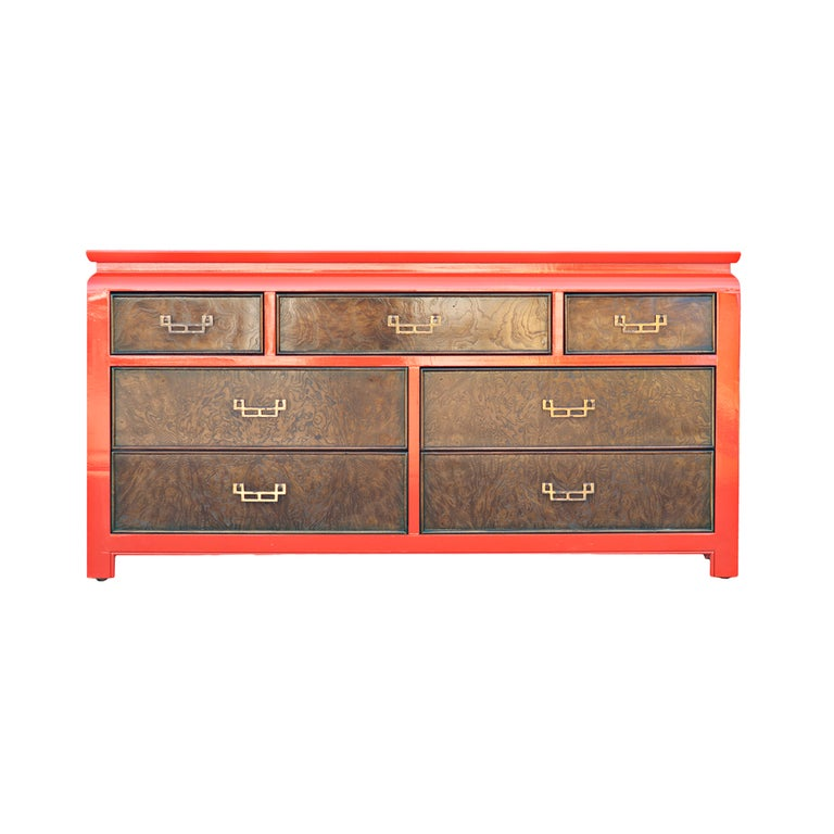A mid century modern dresser made by Century from their Chin Hua series with an Asian motif.  An orange lacquered frame and top with burled ash sides and drawer fronts with bronze pulls.
