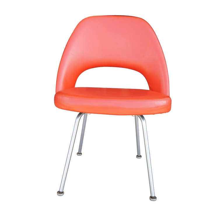 A lovely set of four 72U chairs by Eero Saarinen in a brilliant orange/red, vinyl upholstery.  Legs of tubular steel with glides present.