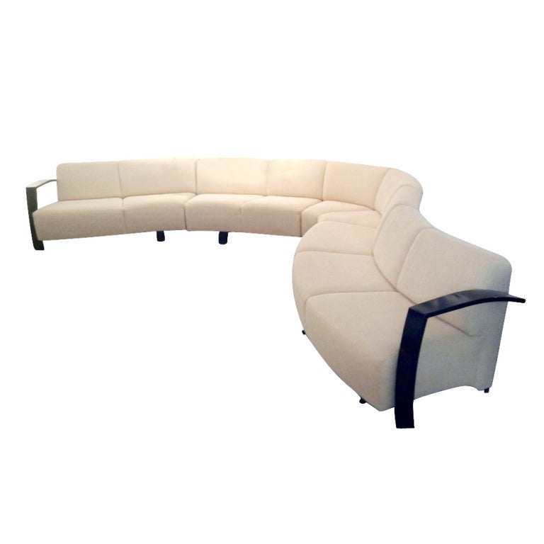 A mid-century modern sectional sofa by Thonet measuring twenty-one feet long.  Four separate sections providing for different serpentine configurations.  Ebonized wooden arms and feet.  Newly upholstered in a textured cream colored fabric.