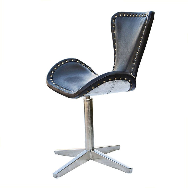 A unusual leather swivel side chair somewhat in the manner of Arne Jacobsen with a four star metal base and brass nailhead accents.  An interesting reinterpretation of a 50`s Danish modern design in silver metal.