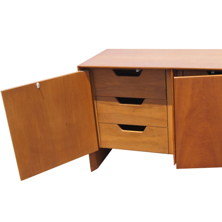A mid century modern buffet designed by T. H. Robsjohn Gibbings and made by Widdicomb.  Made of walnut with three doors, two of them concealing drawers and one with shelved storage.