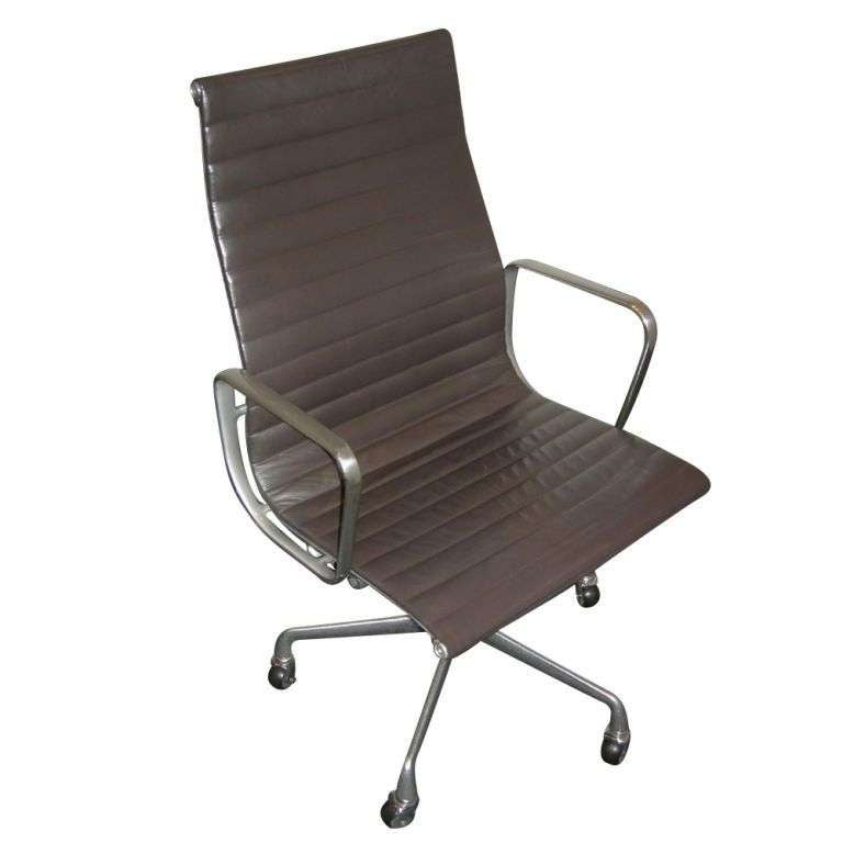 One mid century modern executive chair designed by Charles and Ray Eames for Herman Miller.  The high back model from the Aluminum Group Series.  Brown leather upholstery with aluminum frame and five-star base with casters.  Seat height adjustable
