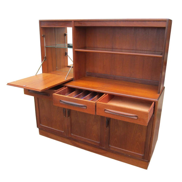 A Danish style multi-use cabinet which functions as a buffet, china cabinet and bar. The bottom section has three doors concealing shelved storage and three drawers, one of which is partitioned for flatware. The top section features shelves and a