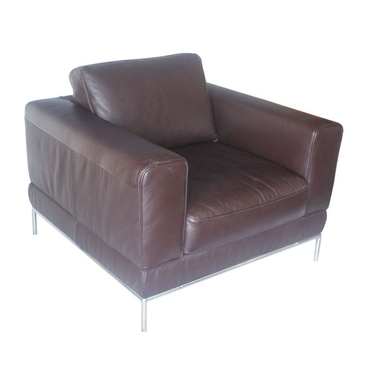 A pair of roomy brown leather lounge chairs with segmented metal base.