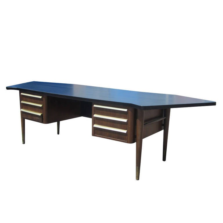 A vintage Stow Davis executive 9 ft desk with a large ebonized curved top. Brass detailing for the three pulls on either side and glides make enhance the presence of this desk.