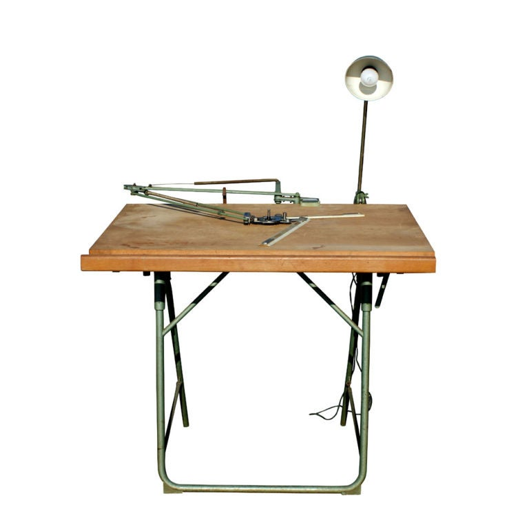 A vintage folding drafting table designed by Christian Dell and made by Franz Kulmann KG in Germany.  A light green metal folding frame with wooden drafting table top and original green metal matching lamp.