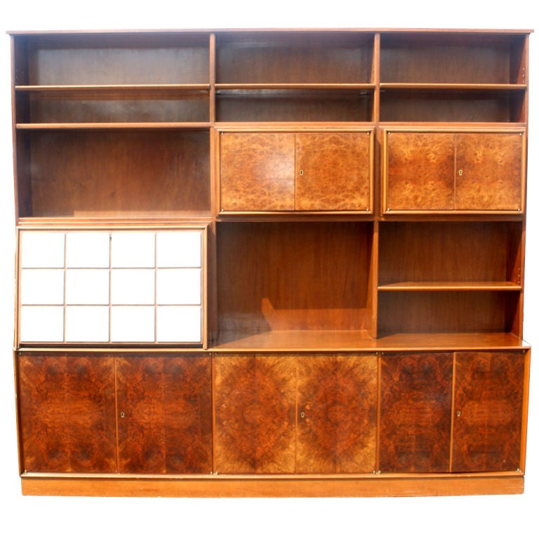 A mid century modern wall unit executed in an exotic burled veneer.  A multi-use piece containing a desk, fitted flatware drawers, and extensive shelved storage both open and concealed.