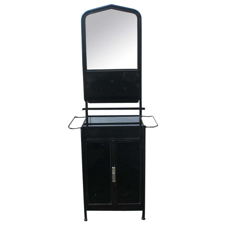 An industrial washstand from the first half of the twentieth century.  Black steel with a mirror, glass shelf, towel racks and ample storage.