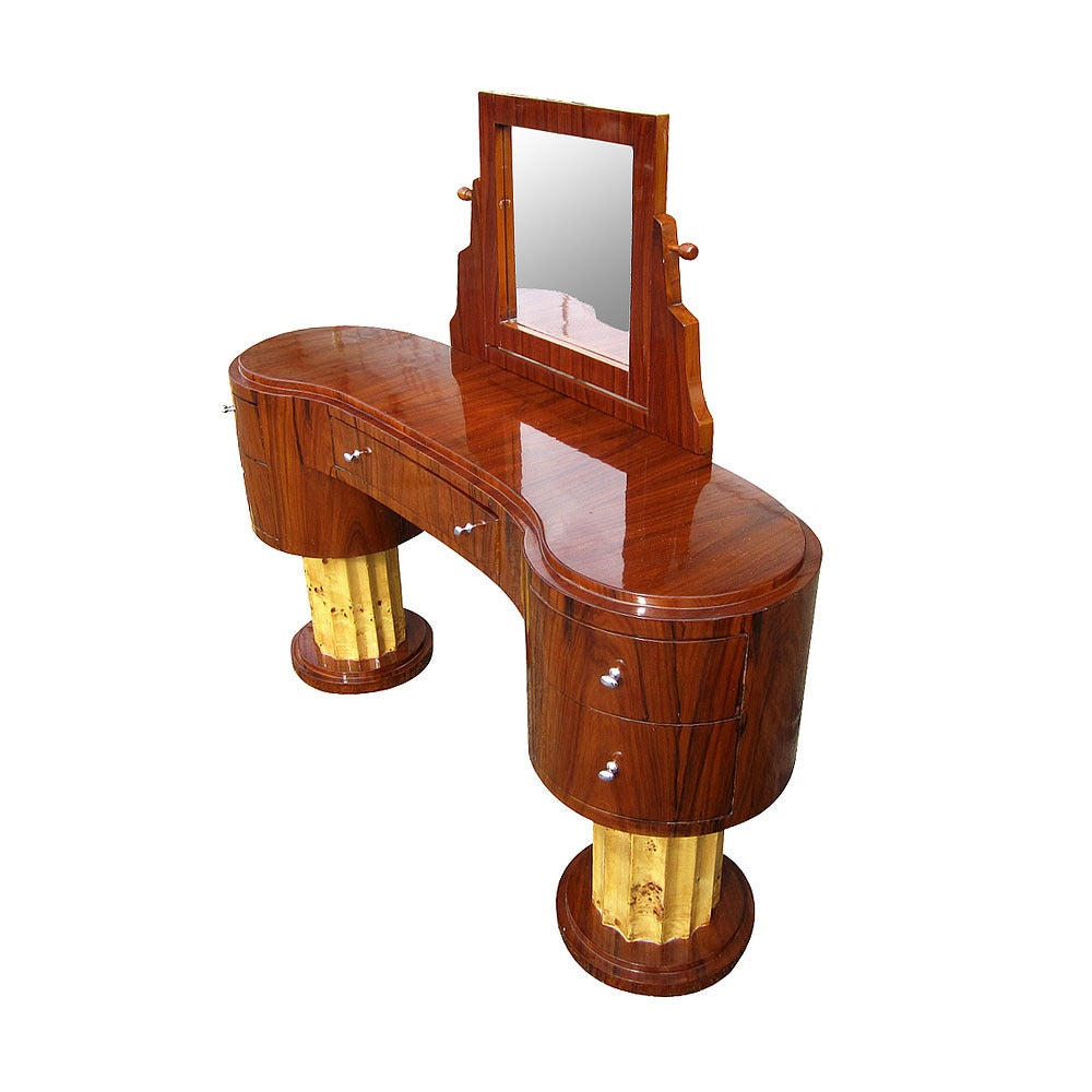 A double-pedestal, art deco vanity with five beautiful drawers, two on each side and a large one in the middle. Furnished with walnut wood and inset with steel pullouts, this piece sports an adjustable flip-mirror and a large, open top fit for
