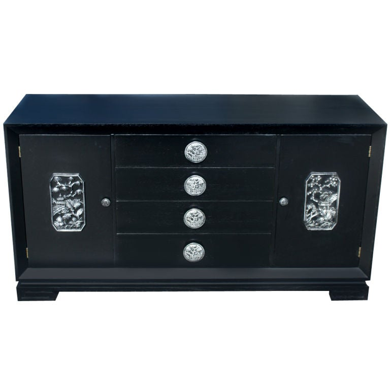 An Asian inspired buffet or cabinet designed by James Mont.  Ebonized oak with silver leaf detailing.  Four center drawers with carved pulls and two side doors with shelved storage.