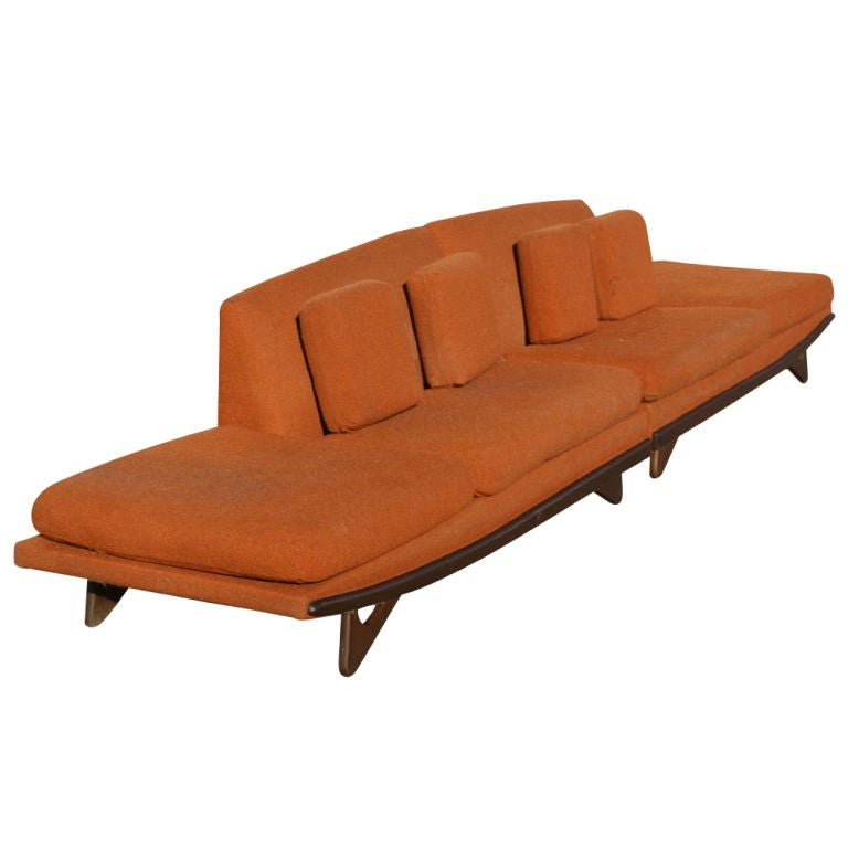 A mid-century modern sectional sofa designed by Adrian Pearsall and made by Craft Associates.  Two 6ft sections that can be positioned end to end for a long sofa or used as two separate sofas.  Sculpted walnut base with orange tweed upholstery.