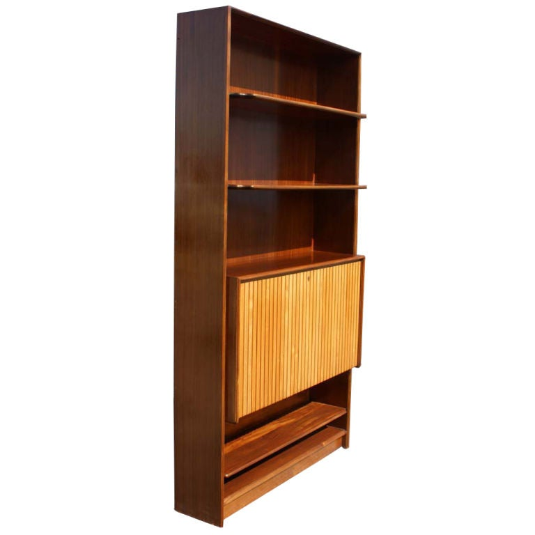 Unique mid-century two-toned Kingwood and Maple bookcase with a hideaway mini bar. The bar features a mirrored platform, 4 side shelves, 2 drawers, and 2 glass serving trays.