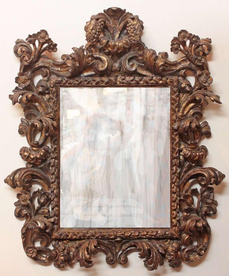 A fine 17th century italian baroque giltwood mirror with for Italian baroque mirror