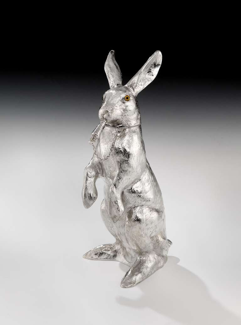 A very detailed and very heavy-gauge solid Sterling silver cocktail shaker by Neresheimer of Germany, in the form of a Hare, realistically modelled sitting up on its hind quarters, the pull-off head with glass eyes, removes to reveal an integral