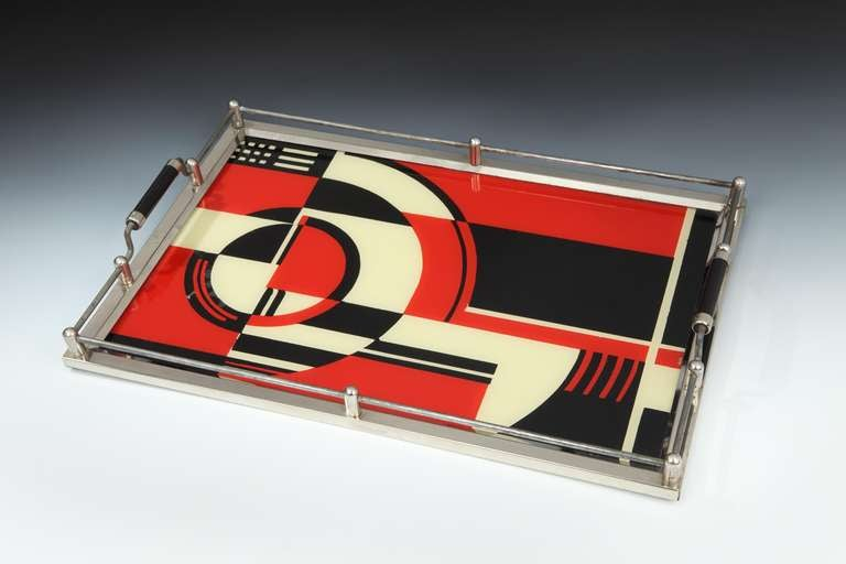 A Modernist design Art Deco cocktail tray with a reverse-painted geometric composition to the glass tray, with a nickelled framework and Bakelite grip handles.   Literature: 'Popular Art Deco', Heide and Gilman (p. 64) published 1991, 'The Machine