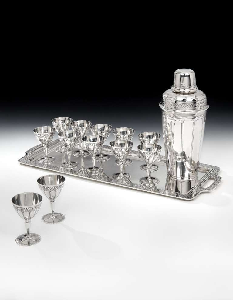 A spectacular Art Deco sterling silver 14-piece cocktail set, comprising of a massive 4½ pint cocktail Shaker, (the largest Tiffany produced), with a highly decorative, foliate pierced strainer and heavy cap, with a suite of 12 cocktail goblets all